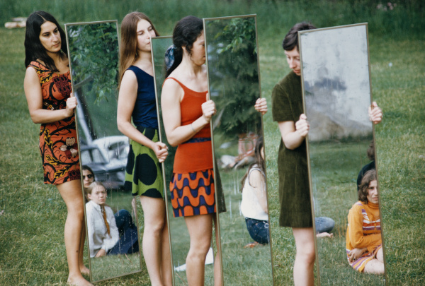A photo of four women standing outside, each holding a full length mirror that reflects other people.